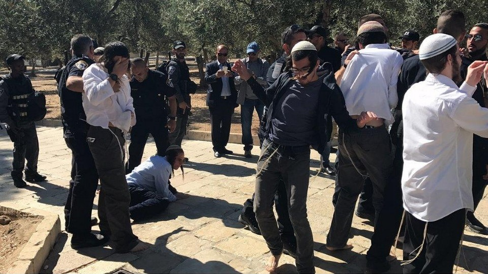 Barefooted Jewish extremists prostrate themselves onto the ground of Al-Aqsa Mosque / Al-Haram Al-Sharif under the protection of armed Israeli police
